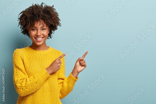 Fototapeta Cheerful Afro woman points away on copy space, discusses amazing promo, gives way or direction, wears yellow warm sweater, has pleasant smile, feels optimistic, isolated over blue background obraz