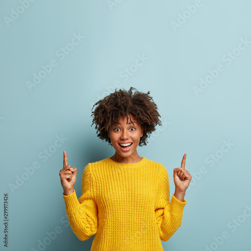 Fotomural  Gorgeous cheerful smiling woman with Afro hairstyle, points up, shows cool promo