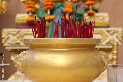 Fotografija  Golden incense burner filled with incense sticks