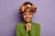 canvas print picture - Studio shot of beautiful young lady smiles happily, keeps hands pressed together, looks hopefully at camera, wears autumnal handmade wreath, casual poloneck, models against purple background