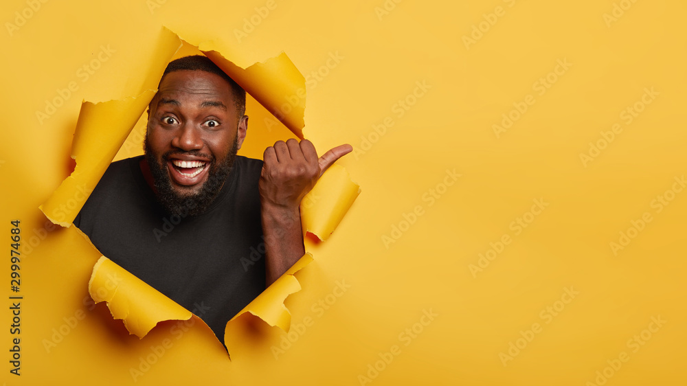 Fototapety, obrazy: Cheerful enthusiastic Afro man with dark skin points thumb aside, laughs and introduces promo, recommends best offer, dressed in black clothing, poses through torn paper hole, yellow background