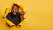 Cheerful enthusiastic Afro man with dark skin points thumb aside, laughs and introduces promo, recommends best offer, dressed in black clothing, poses through torn paper hole, yellow background