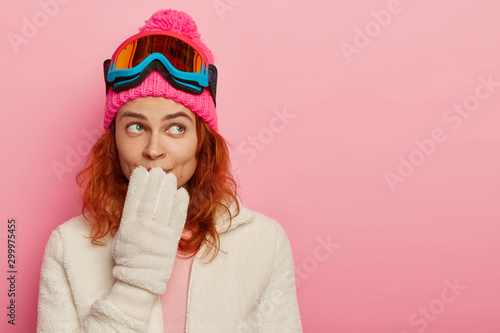 Obraz na plátne  Portrait of snowboarder woman has thoughtful expression, keeps hand on mouth, we