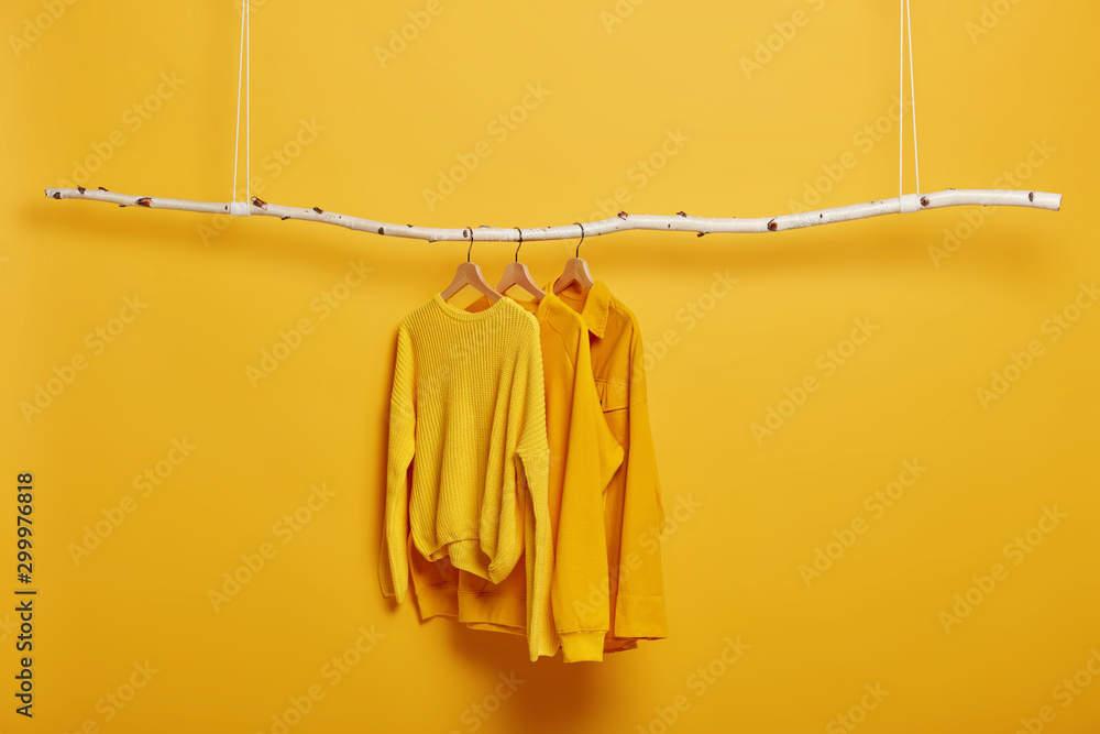 Fototapety, obrazy: Selective focus. Three items of clothes on hangers. Long sleeved yellow jumpers on wooden rack near bright vivid wall. Copy space for text. Various casual outfits hanging in row at dressing room