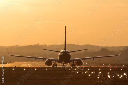 Obraz Lądowanie samolotu na lotnisku o zachodzie słońca - fototapety do salonu