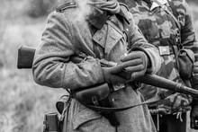 German Wehrmacht Soldier In Overcoat With A Rifle In His Hands And A Cigarette. Black And White Shot