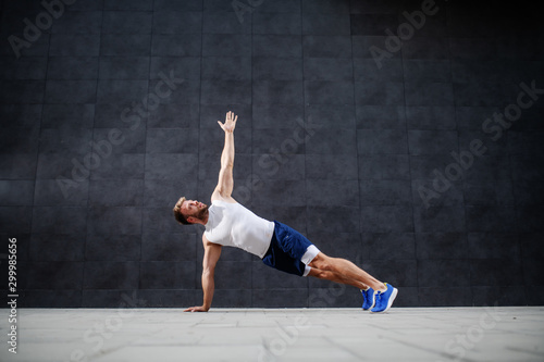 Obraz Handsome sporty caucasian man in shorts and t-shirt stretching his arm in plank position in front of gray wall. - fototapety do salonu