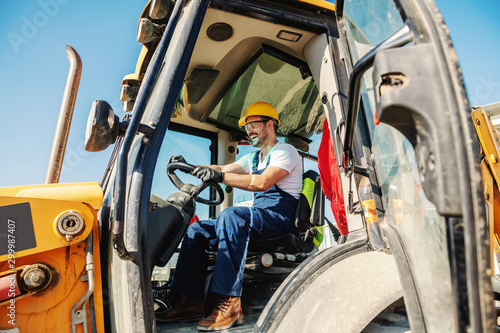 Fotomural Smiling handsome caucasian worker in overall and with helmet on head driving excavator