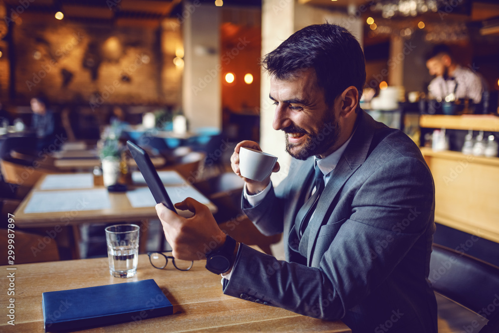 Fototapety, obrazy: Handsome smiling caucasian bearded businessman in suit sitting in cafe, drinking coffee and using tablet.