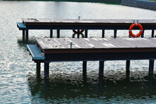 Wooden Pier With Lifebuoys. Autumn Cozy Water Landscape With A Pier For Boats.