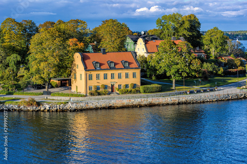 Obraz na plátne Yellow ancient house with red tiled roofs on waterfront of island Djurgarden at bright sunny day with autumn forest on the background