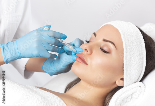 Photo The doctor cosmetologist makes Lip augmentation procedure of a beautiful woman in a beauty salon
