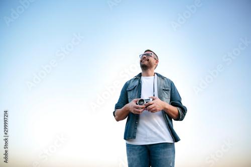 Photo Hombre joven y sonriente con cámara de fotos analógica sobre cielo azul
