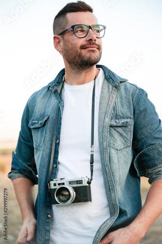 Photo Hombre joven y sonriente con cámara de fotos analógica en medio de un desierto