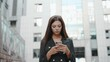 Young adult businesswoman using smartphone in city