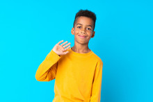 African American Boy Over Isolated Blue Background Saluting With Hand With Happy Expression