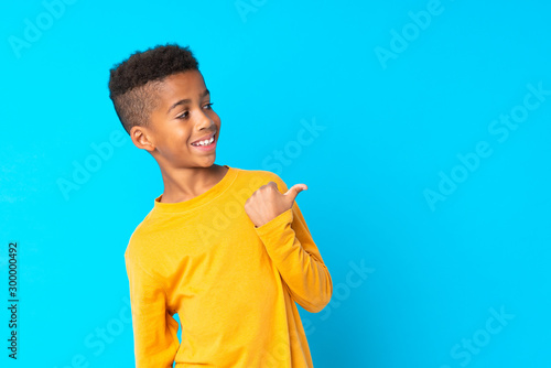 Fototapeta African American boy over isolated blue background pointing to the side to present a product obraz