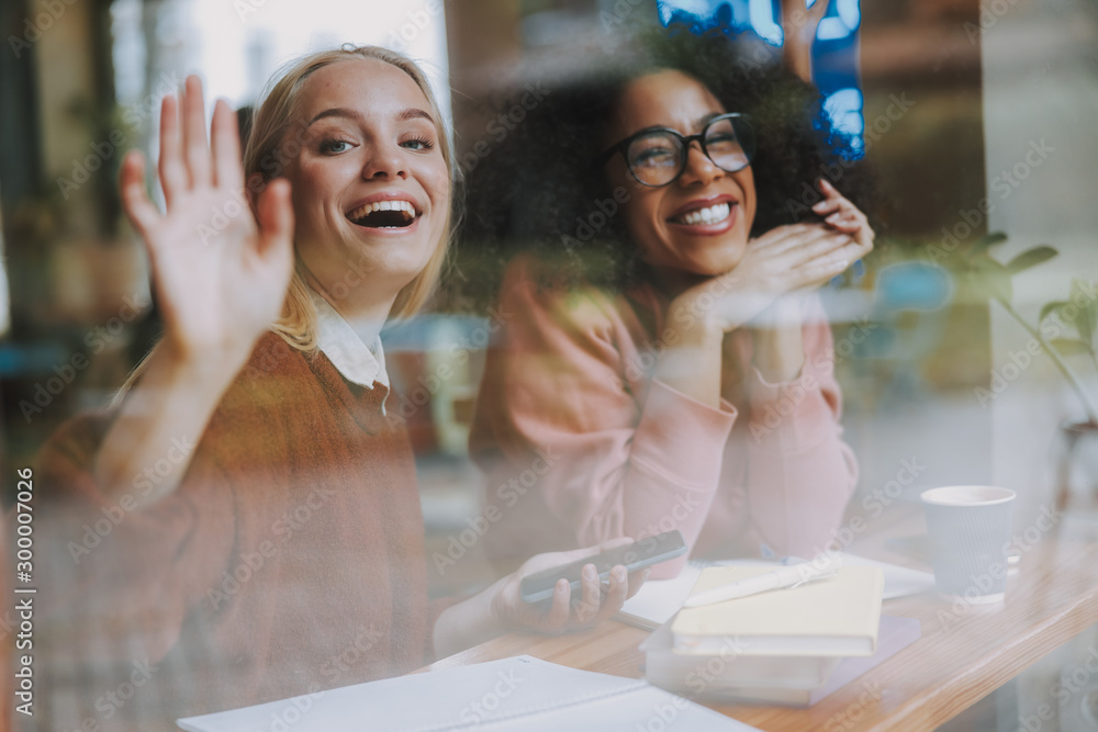 Fototapety, obrazy: Two young females waving hand and smiling wide