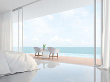 Modern Luxury White Bedroom 3d Render.There Is A Minimalistic Building With White Beds And Chairs. There Is A Large Open Sliding Door Overlooking The Infinity Pool And Sea View.