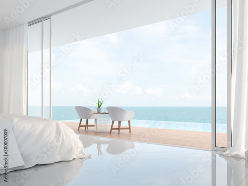 Fototapeta Modern luxury white bedroom 3d render.There is a minimalistic building with white beds and chairs. There is a large open sliding door overlooking the infinity pool and sea view. obraz