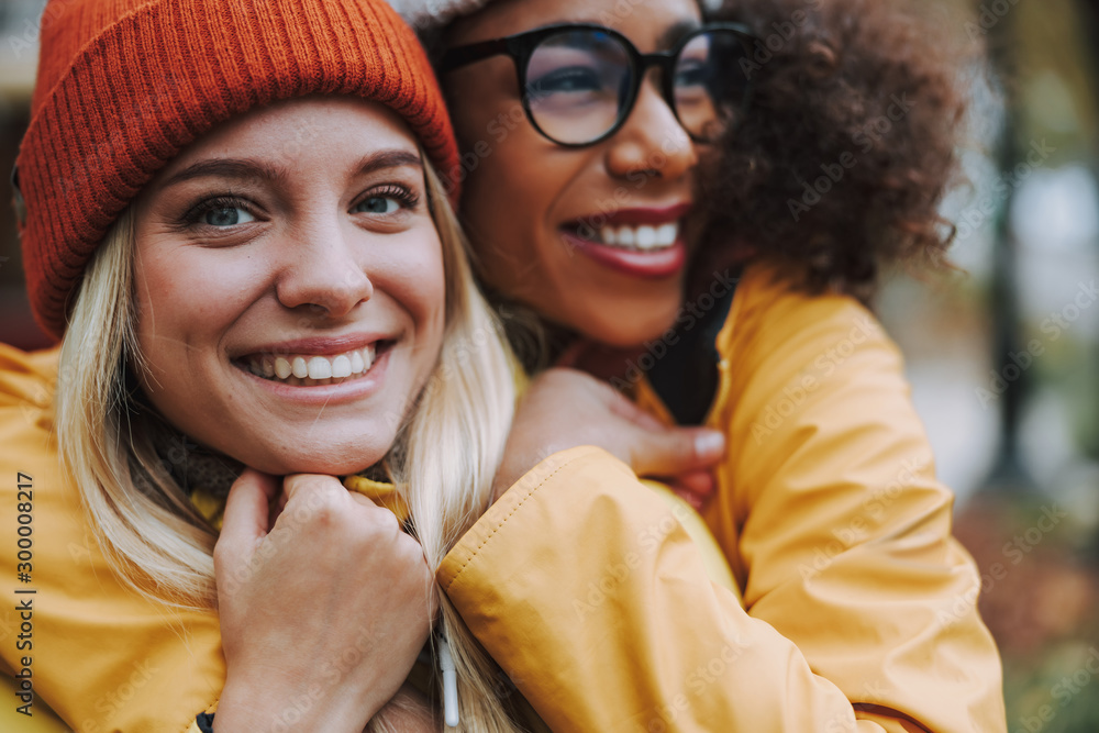 Fototapeta Two young ladies hugging and smiling wide outdoors
