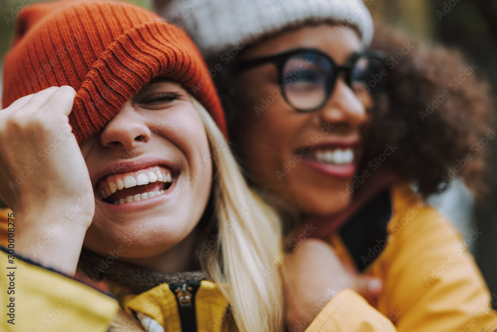 Fototapeta Two young females laughing and hugging in park