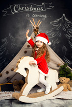Little Girl In Santa Costume On A Rocking Horse Is Ready To Celebrate The Holidays