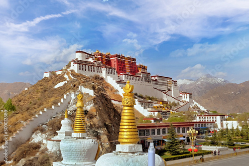 Lateral view of the Potala Palace in Lhasa, Tibet, surrounded by green vegetation, against a blue summer sky covered by white clouds.