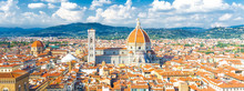 Top Aerial Panoramic View Of Florence City With Duomo Cattedrale Di Santa Maria Del Fiore Cathedral, Buildings Houses With Orange Red Tiled Roofs And Hills Range, Blue Sky White Clouds, Tuscany, Italy