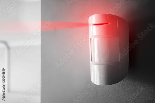 Modern motion sensor on wall indoors