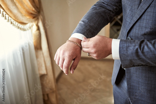 Poster de jardin Vache Businessman wears a jacket,male hands closeup,groom getting ready in the morning before wedding ceremony