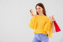Beautiful Young Woman With Shopping Bags And Credit Card On Light Background