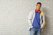 Leinwandbild Motiv Portrait of African-American teenage schoolboy on brick background
