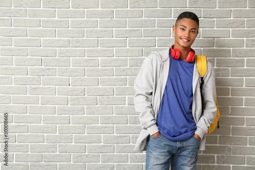 Portrait of African-American teenage schoolboy on brick background Wallpaper Mural