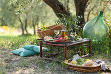 Romantic Picnic Under Olive Tree. Delicious Italian Meal Served On A Wooden Table. Baskets With Food, Branches In Glass Jar. Sunny Autumn Day. Italy, Tuscany