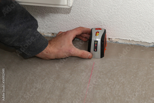 Valokuva  Man using cross-line laser to mark the floor
