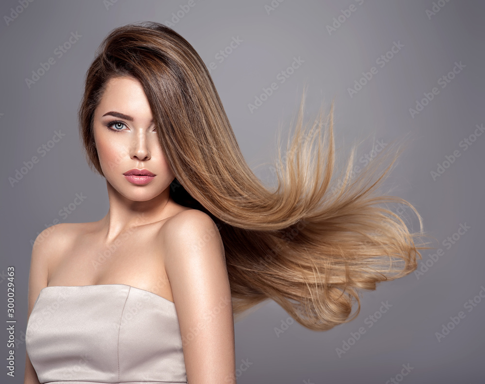 Fototapeta Young woman with long straight hair. Blond girl.