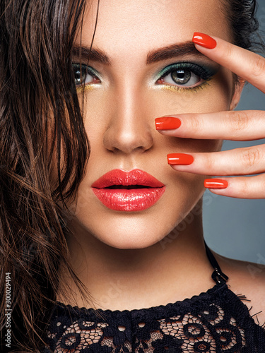Beautiful woman with bright red lipstick on her lips. Gorgeous girl with blue eye makeup. Portrait of an attractive girl with orange nails on her face. Fashion  model. Sexy face of a pretty lady.