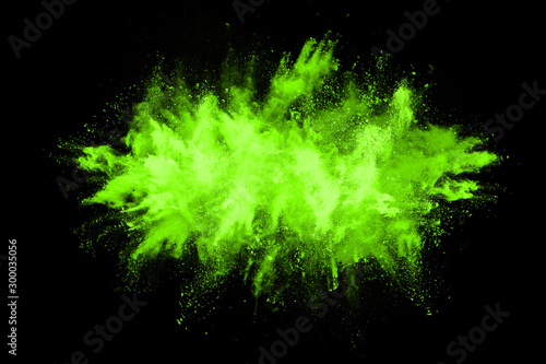 The movement of abstract dust explosion frozen green on black background. Stop the movement of powdered green on black background. Explosive powder green on black background. - 300035056