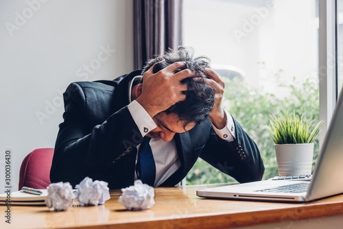 Obraz na plátně  Asian young business man tired strain failure on he work