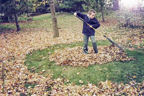 Fotografia Boy raking leaves in a yard doing chores