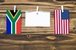 canvas print picture - Hanging flags of South Africa and United States attached to rope with clothes pins with copy space on white note paper on wooden background.Diplomatic relations between countries.