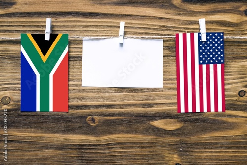 canvas print motiv - sezerozger : Hanging flags of South Africa and United States attached to rope with clothes pins with copy space on white note paper on wooden background.Diplomatic relations between countries.