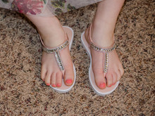 Young Girl's Feet Wearing Sparkle Fancy Shoes.  Child's Toe Nails Painted Pink. Toddler Toes With Pedicure Wearing Cute Summertime Sandals.