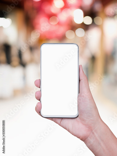 Fototapeta Hand holding smartphone with abstract blur shopping mall background