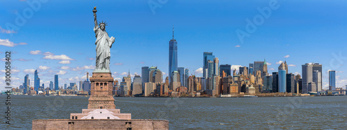 Obraz The Statue of Liberty over the Panorama Scene of New York cityscape river side which location is lower manhattan, United state of America, USA, Architecture and building with tourist concept - fototapety do salonu