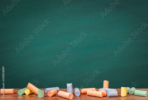 Group of colorful chalks and a blackboard or chalkboard background, concept for education, banner, startup, teaching , etc.