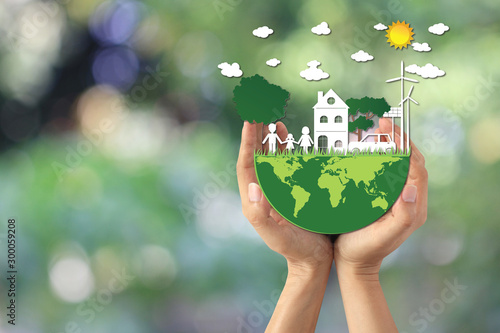 Man hand holding green world with model house and model family on natural green background, We love the world of ideas
