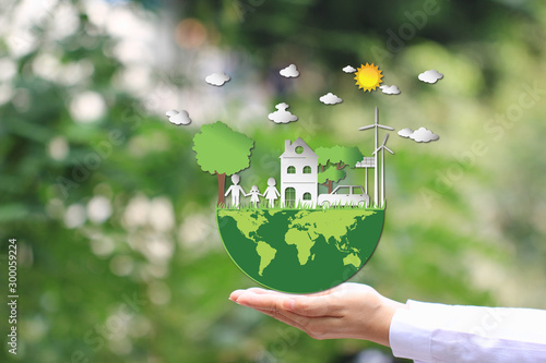 Woman hand holding green world with model house and model family on natural green background, We love the world of ideas