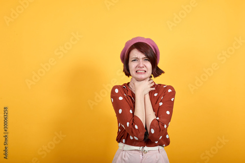 Young beautiful caucasian woman over isolated yellow background shouting and suffocate because painful strangle Wallpaper Mural